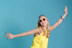 Portrait of beautiful blond woman in sunglasses and yellow shirt dancing on blue background. Carefree summer. Royalty Free Stock Photography