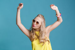 Portrait of beautiful blond woman in sunglasses and yellow shirt dancing on blue background. Carefree summer. Stock Photos
