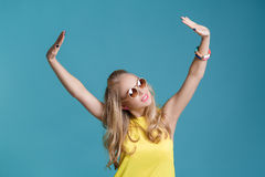 Portrait of beautiful blond woman in sunglasses and yellow shirt dancing on blue background. Carefree summer. Stock Photography