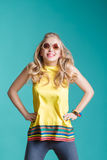 Portrait of beautiful blond woman in sunglasses and yellow shirt jumping on blue background. Carefree summer. Stock Photography