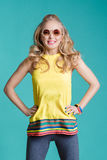 Portrait of beautiful blond woman in sunglasses and yellow shirt jumping on blue background. Carefree summer. Royalty Free Stock Photography
