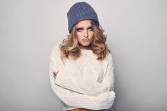 Portrait of beautiful blond woman. In white in white sweater and blue hat Stock Images