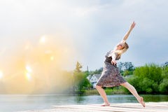 Portrait of beautiful blond young lady dancing like angel in light dress at water lake and sun lighting miracle flare. Picture of beautiful blond girl dancing Royalty Free Stock Photography
