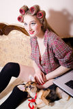 Portrait of beautiful blond young woman with curlers on her head with red lips and blue eyes in shirt with little funny puppy dog. Pretty sexy girl with curlers Royalty Free Stock Photo