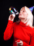 Portrait of a beautiful blonde blowing bubbles. Attractive happy girl blowing bubbles at party Royalty Free Stock Photos