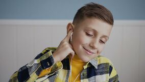 Portrait. A beautiful blonde boy 7-8 year listening to music in the white headphones, he dancing nodding his head. Close. Up. In white background, indoors, slow stock footage