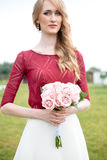Portrait of beautiful blonde bride with bouquet of pink roses Stock Image
