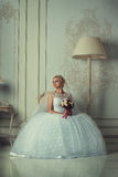 Portrait of a beautiful blonde bride. Beautiful bride in an elegant dress sitting in an ancient chair in luxury interior Royalty Free Stock Images