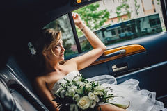Portrait of a beautiful blonde bride sitting in  wedding car and looking at somebody or something through the window Royalty Free Stock Images