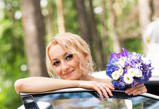 Portrait of a beautiful blonde bride with the wedding car. Stock Images