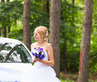 Portrait of a beautiful blonde bride with the wedding car. Royalty Free Stock Photo