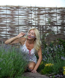 Portrait of a beautiful blonde with flowers in the garden Stock Images