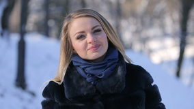 Portrait of Beautiful Blonde Girl. Portrait of attractive beautiful blonde girl smiling and posing to camera in winter park stock video footage