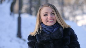 Portrait of Beautiful Blonde Girl. Portrait of attractive beautiful blonde girl smiling and posing to camera in winter park stock footage