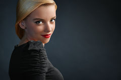 Portrait of beautiful blonde girl on dark blue bac Stock Photo