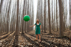 Beautiful blonde girl, dressed in green, walking into the forest Royalty Free Stock Photography