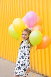 Portrait of a beautiful blonde girl with gel colored balls on a. Yellow background outdoors in summer royalty free stock photography