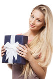 Blonde girl holding gift box. Portrait of a beautiful blonde girl holding blue gift box, looking at camera Royalty Free Stock Photography