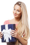 Blonde girl holding gift box. Portrait of a beautiful blonde girl holding blue gift box and smiling, looking at camera Royalty Free Stock Photography