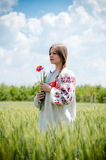 Portrait of beautiful blonde girl holding flowers in her hands standing in field happy smiling & looking at copy space Royalty Free Stock Photos