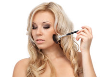 Portrait of a beautiful blonde girl with makeup brush royalty free stock images