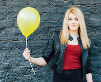 Portrait of a beautiful blonde girl near a black brick wall with a yellow balloon with warm sunny day Stock Photography