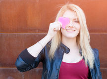 Portrait of a beautiful blonde girl with one hand closes the eyes pink paper heart. Filter, light leak effect. Royalty Free Stock Photos