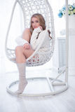 Portrait of beautiful blonde girl in pullover. Inside. The girl sits in an armchair and looking at the camera Royalty Free Stock Photography