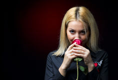 Portrait of a beautiful blonde girl smelling a red rose Stock Photo