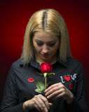 Portrait of a beautiful blonde girl smelling a red rose  Stock Photos