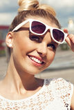 Portrait of beautiful blonde girl in sunglasses on background blue sky Royalty Free Stock Photography