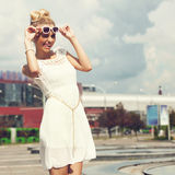 Portrait of beautiful blonde girl in sunglasses on background blue sky Stock Image