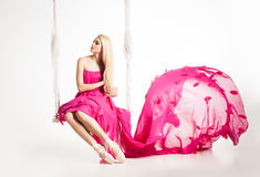 Portrait of beautiful blonde girl on swing in bright pink dress Royalty Free Stock Photo
