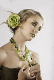 Portrait of beautiful blonde  in green with beaded necklace Royalty Free Stock Images