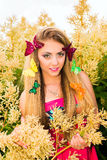 Portrait of beautiful blonde with green eyes. With flowers and butterfly in her hair Stock Photos