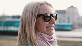 Portrait of beautiful blonde hair Caucasian woman. Happy smiling pretty young 20s girl in stylish sunglasses side view. Slow motion portrait of beautiful blonde stock video footage