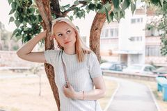 Portrait of a beautiful blonde hair woman near a tree. Romantic portrate of beautiful young woman stock image