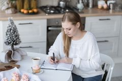 Portrait of a girl writing notes to notebook stock photo