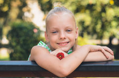 Portrait of the beautiful blonde little girl with a red flower. Outdoor photography royalty free stock photos