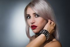 Portrait of a beautiful blonde with red lips a collar with spik. Portrait of a beautiful blonde with red lips on a dark background in a collar with spikes royalty free stock photography