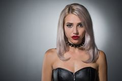 Portrait of a beautiful blonde with red lips a collar with spik. Portrait of a beautiful blonde with red lips on a dark background in a collar with spikes stock photos