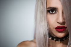 Portrait of a beautiful blonde with red lips a collar with spik. Portrait of a beautiful blonde with red lips on a dark background in a collar with spikes stock photography