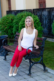 Portrait of a beautiful blonde in red pants Royalty Free Stock Photo