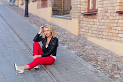 Portrait of a beautiful blonde in red pants Stock Images