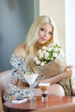 Portrait of a beautiful blonde smiling with flowers Stock Image