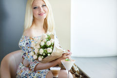 Portrait of a beautiful blonde smiling with flowers Royalty Free Stock Image