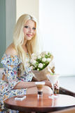 Portrait of a beautiful blonde smiling with flowers Stock Photo
