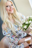 Portrait of a beautiful blonde smiling with flowers Stock Images