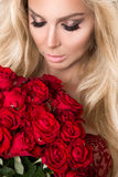 Portrait of the beautiful blonde woman and amazing looks and long hair, perfect skin, keeps the face of a bouquet of red roses , v Stock Photos