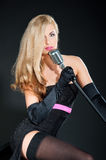 Portrait of a beautiful blonde woman in black dress and gloves with a retro microphone Royalty Free Stock Photography